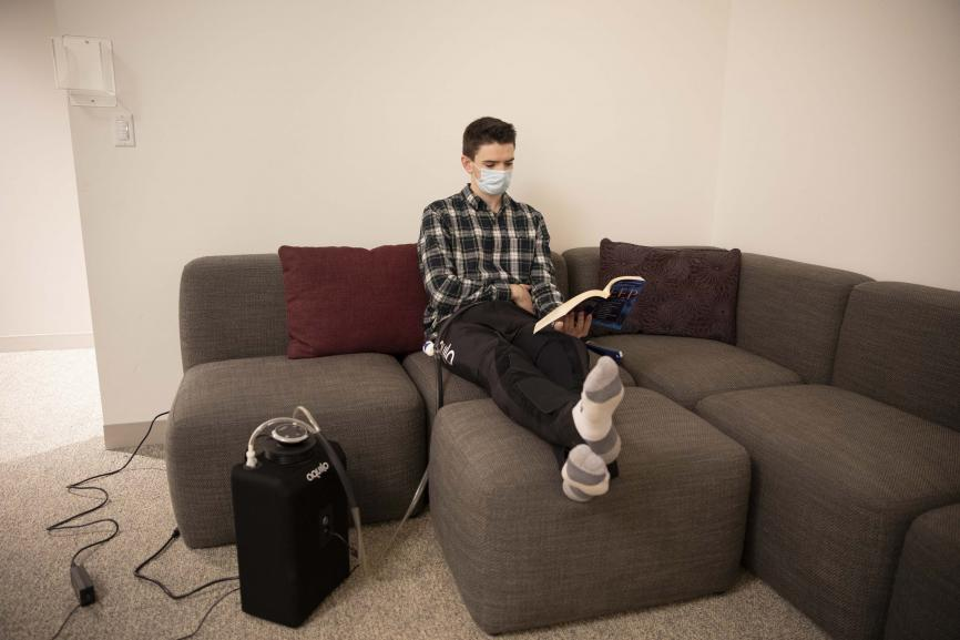 man sitting on couch wearing face mask reading book