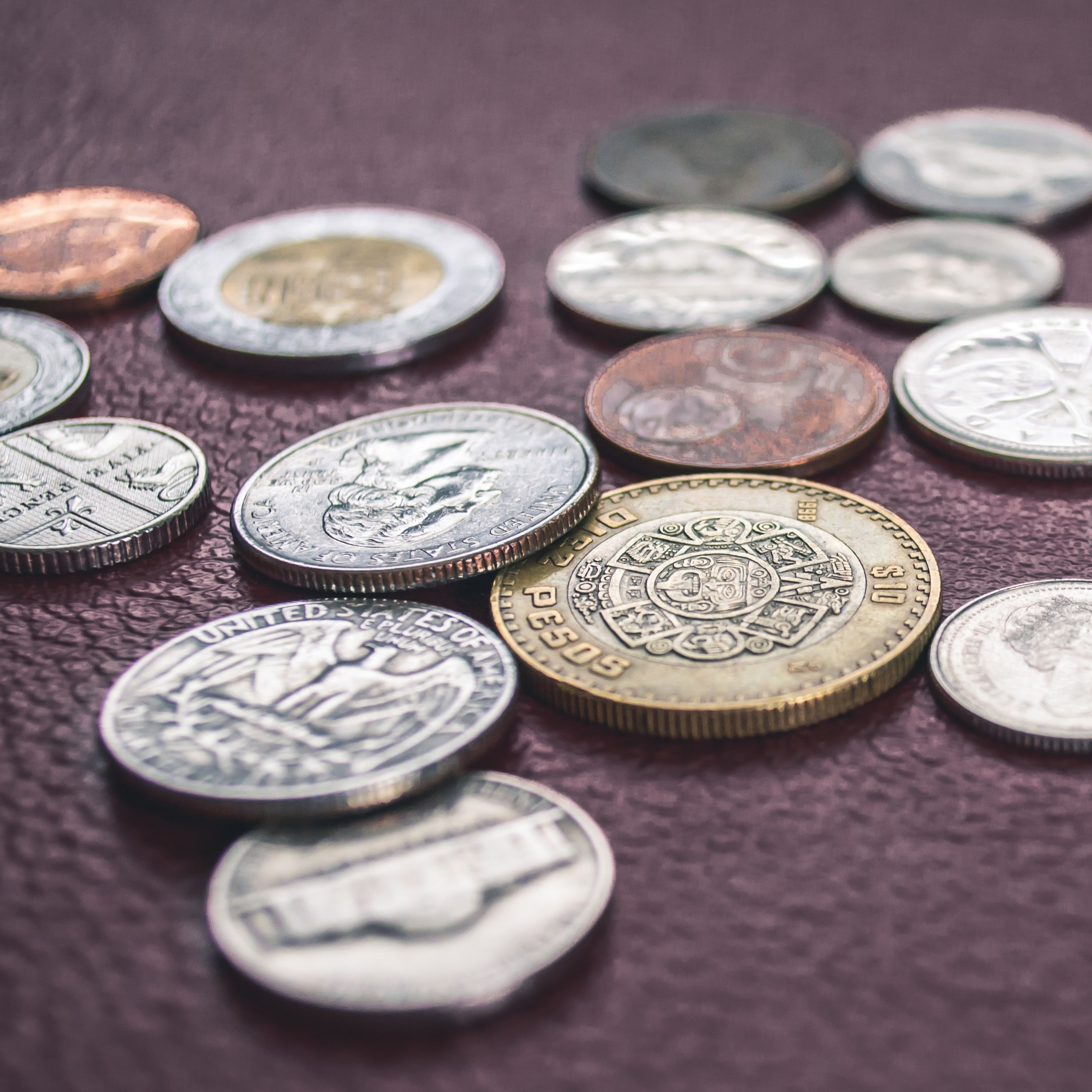 Coins from currencies around the world, scattered on a table.
