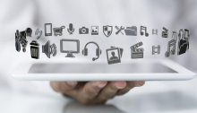 Digital Storytelling stock photo - hand holding white tablet computer with media/communication icons floating above