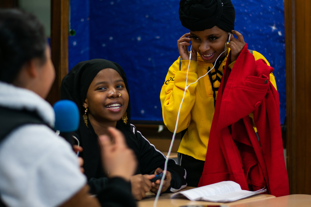 UMass student helping high school journalism students fine-tune their skills