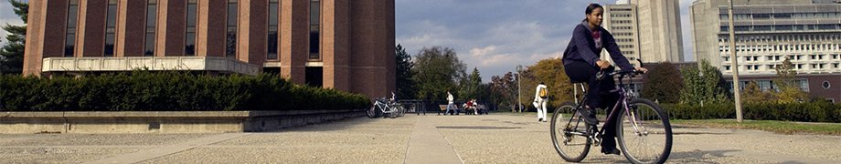 Student riding bike on UMass Amherst campus