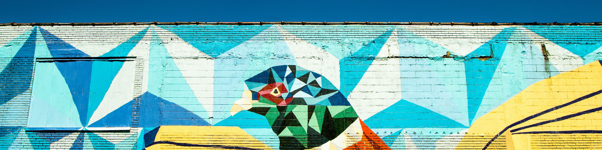 top of mural with bird and shapes with blue skies behind it