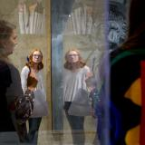 Professor showing an art exhibit while red head student observes