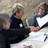 Three Women look over materials at a table