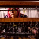 Woman weaving with recycled textiles