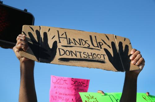 "Hands holding a sign that says ""Hands Up Don't Shoot"""