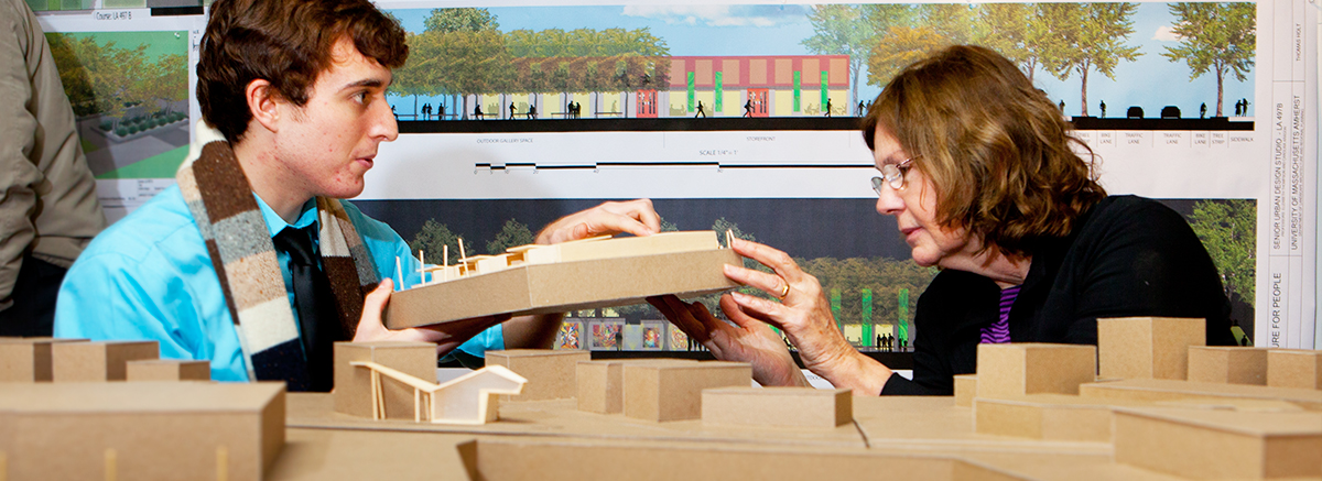 Instructor examining a building model presented by a student.