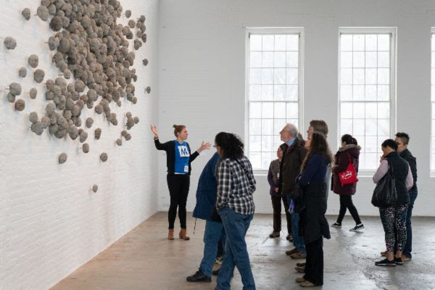 A Mass MoCA Intern in a blue M t-shirts leads a tour group