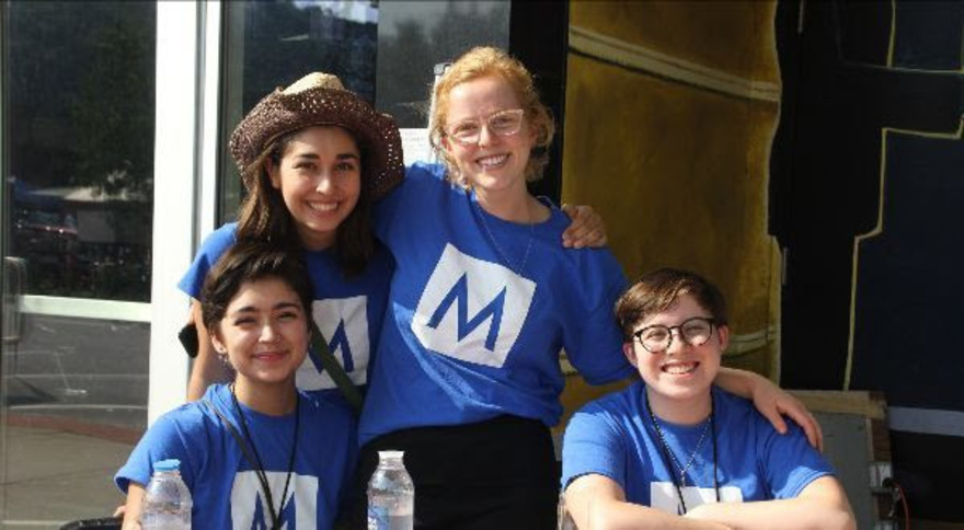 Four Mass MoCA Interns in blue M t-shirts smiling