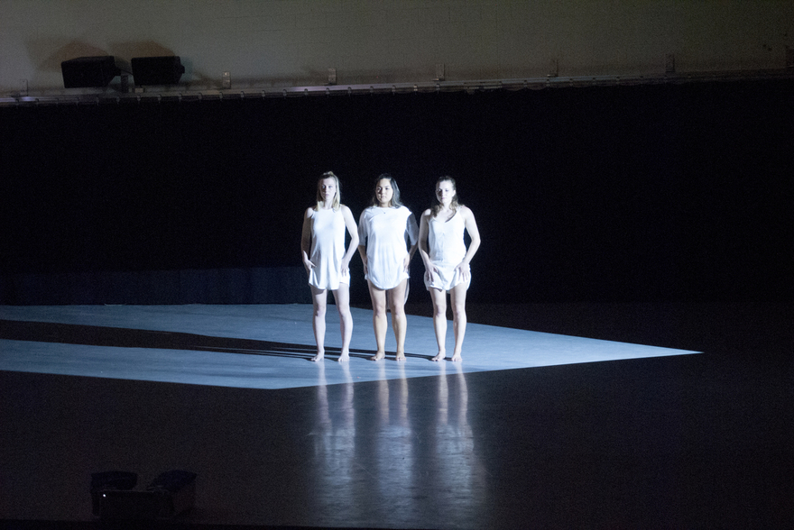 Three dancers stand in a spotlight on an empty stage