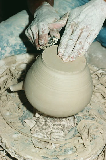 A potter sculpts a container using a pottery wheel