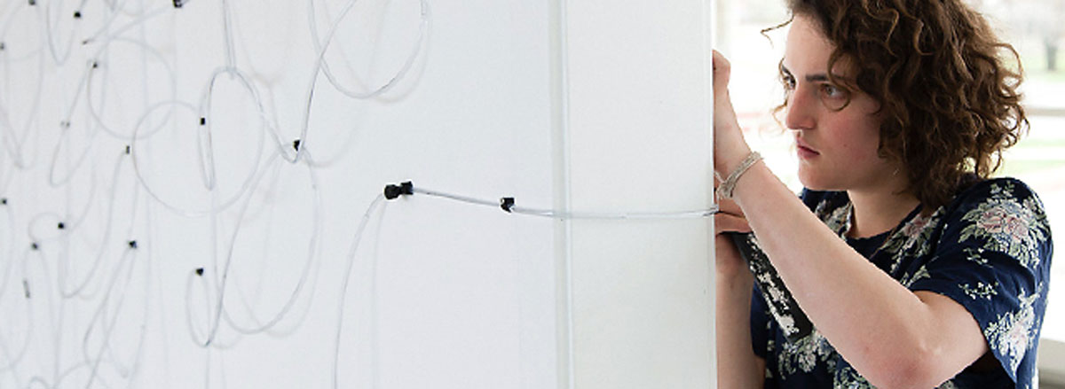 A student pins string to posterboard