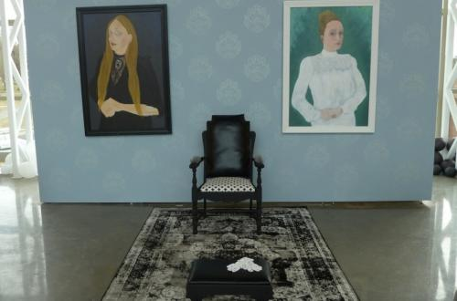 Two paintings of people on a blue backdrop, with a chair set in front and between them