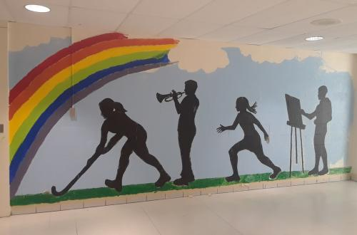 Wall mural depicting four silhouettes engaged in sports, music or art against a blue backdrop with a rainbow.