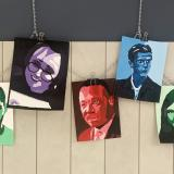 7 paintings of famous people painted with mainly one color of different shades for each work, strung together with a chain, hanging from a fence-like board