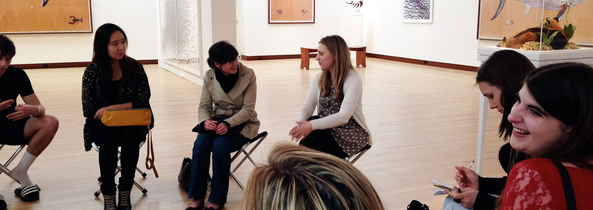 Students discussing artwork in a museum setting