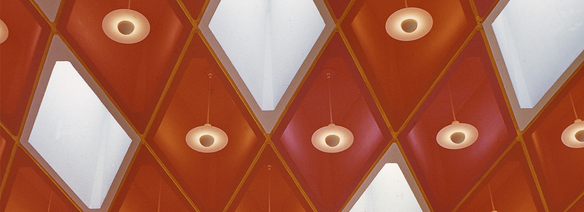 Patterned ceiling tiles and hanging lamps.