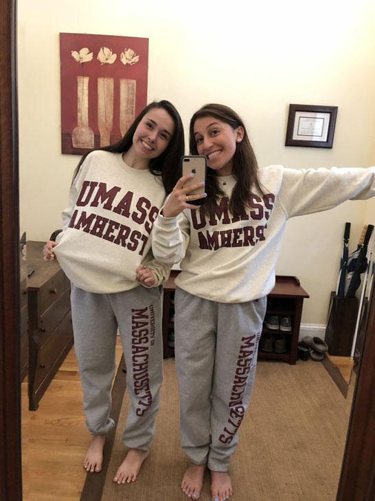 Two women taking a selfie wearing matching umass sweatsuits