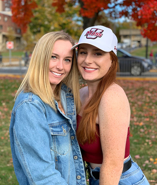 Two women posing on campus in the fall