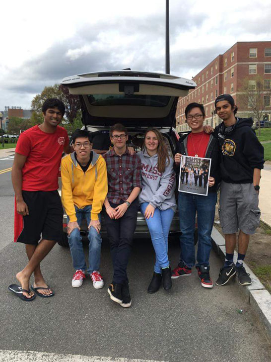 Six student posing on tailgate holding photo of them in tuxedo's and gown