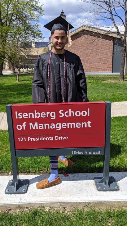 Student wearing cap and gown in front of Isenberg School of Management sign showing his 2020 socks