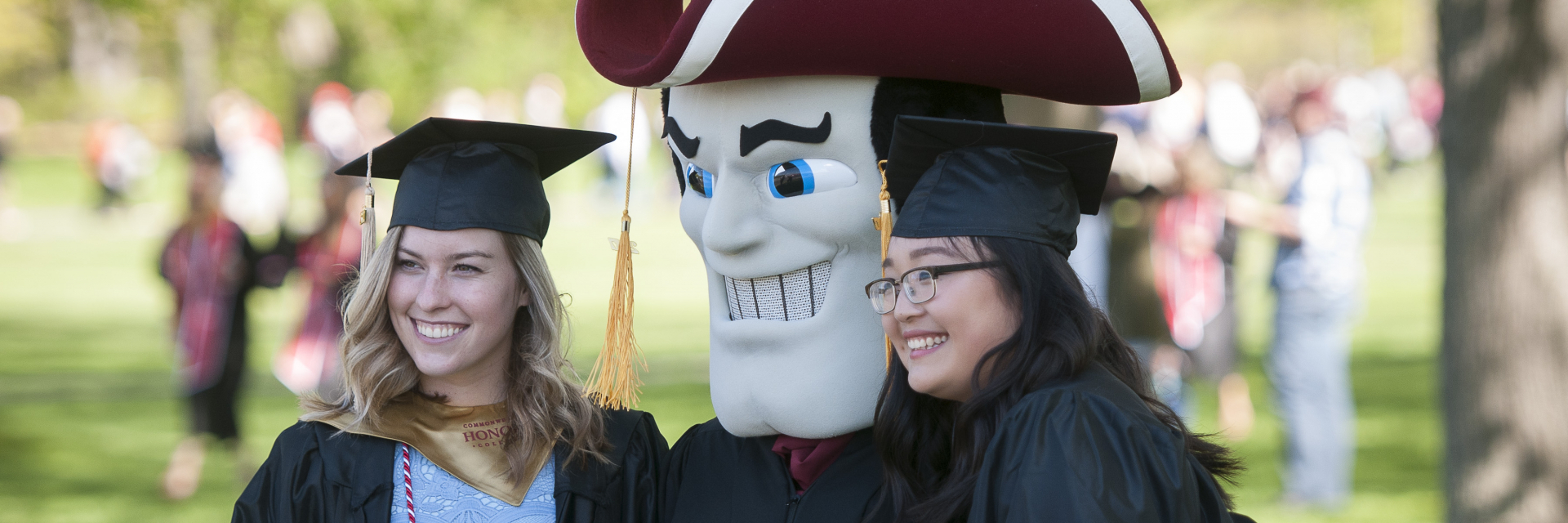 Students with Sam the Minuteman at UMass Undergraduate Commencement
