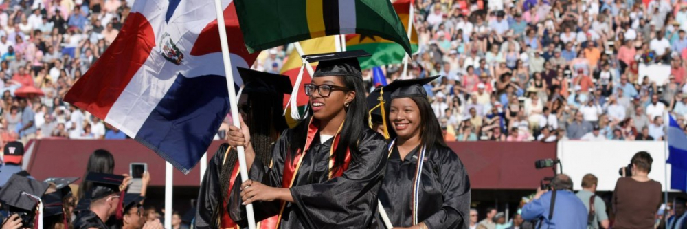 Two women of color holding flags at commencement