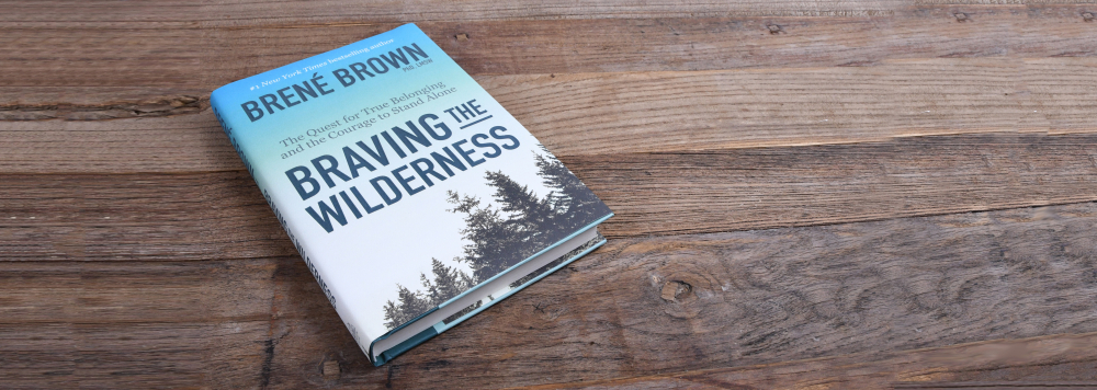 "Brene Brown's book ""Braving the Wilderness"" on a wood table"