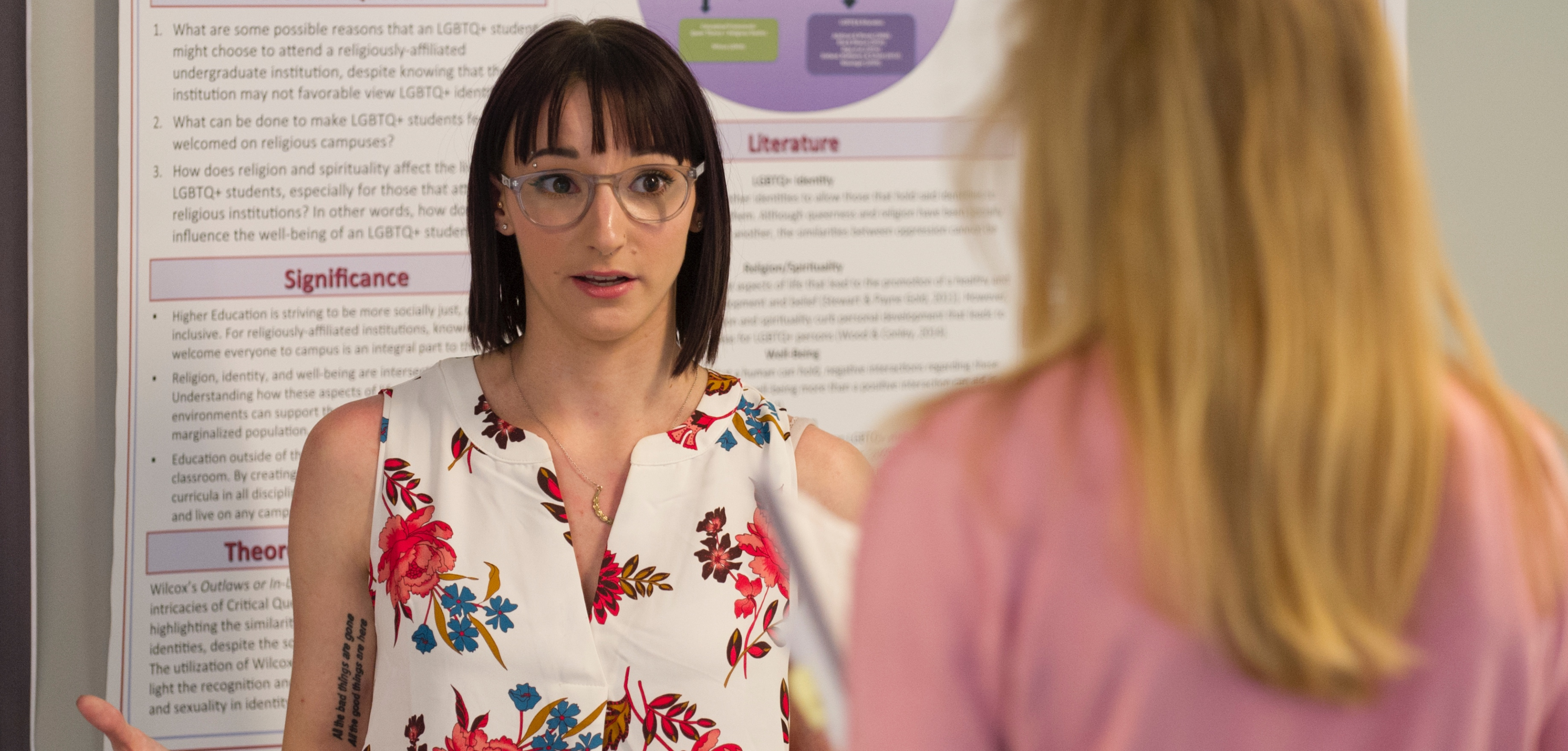 student presenting research at poster event