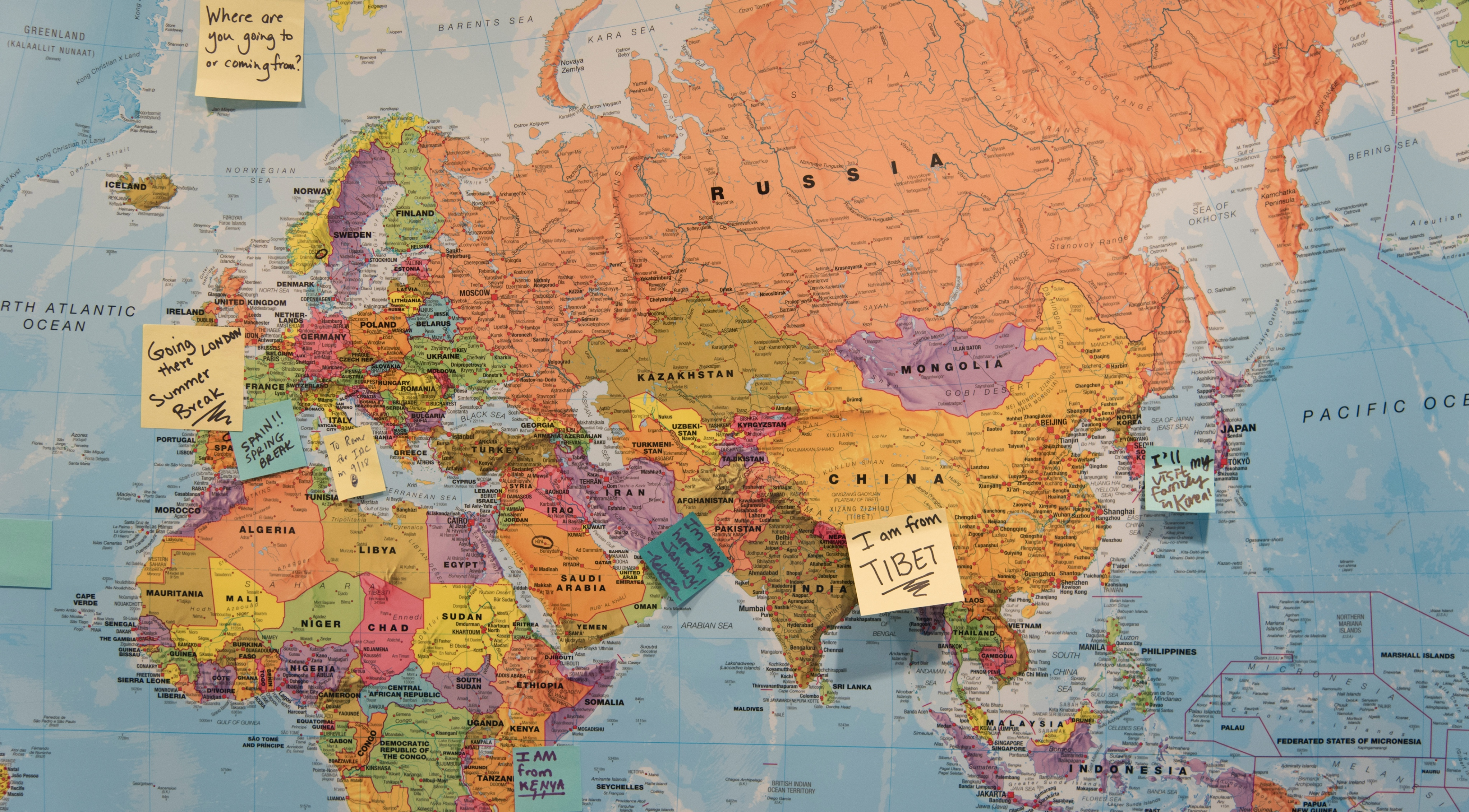 map of the world with post-it notes on countries where people have traveled