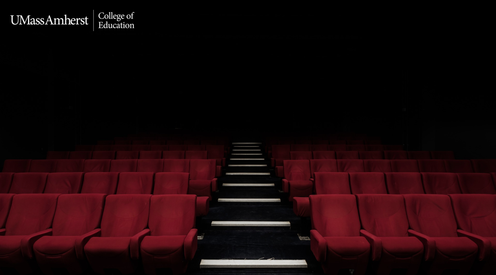An empty auditorium with the College of Education logo