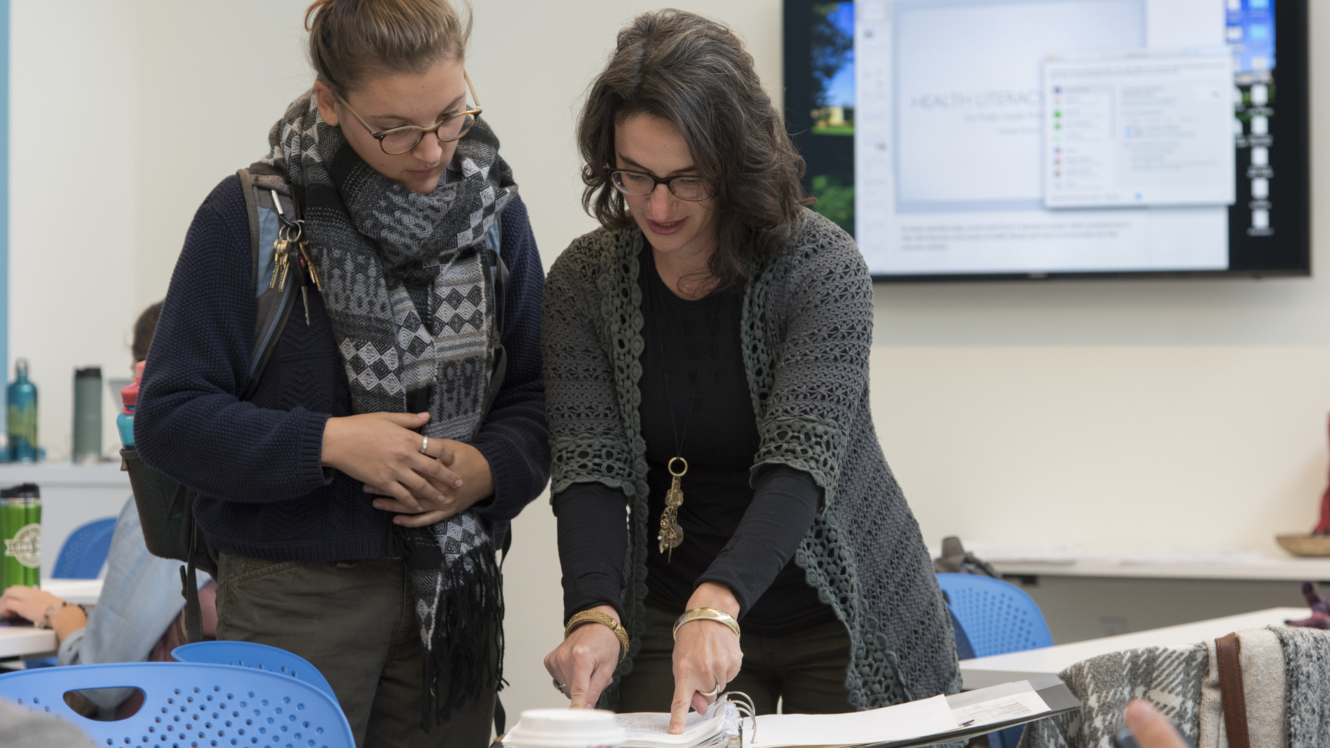 faculty member and student looking at papers in a three-ring binder