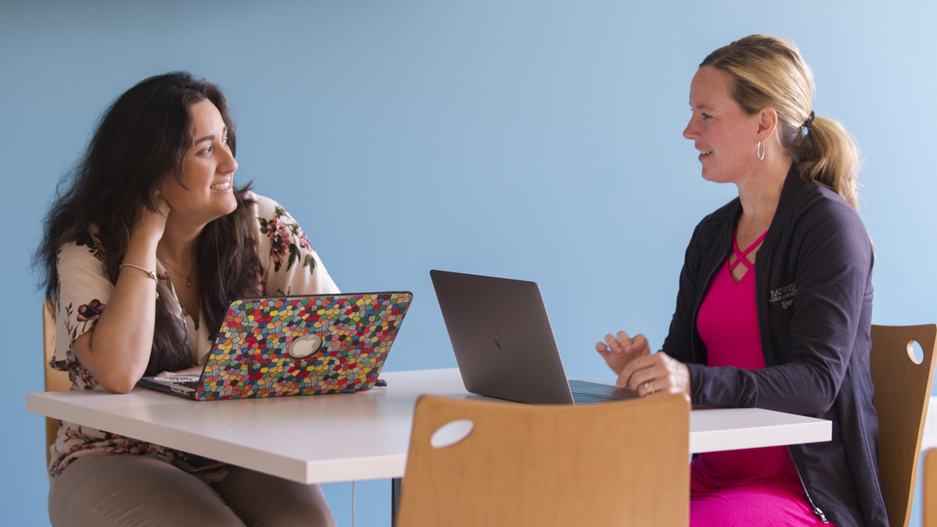 Two students talking while working on laptops