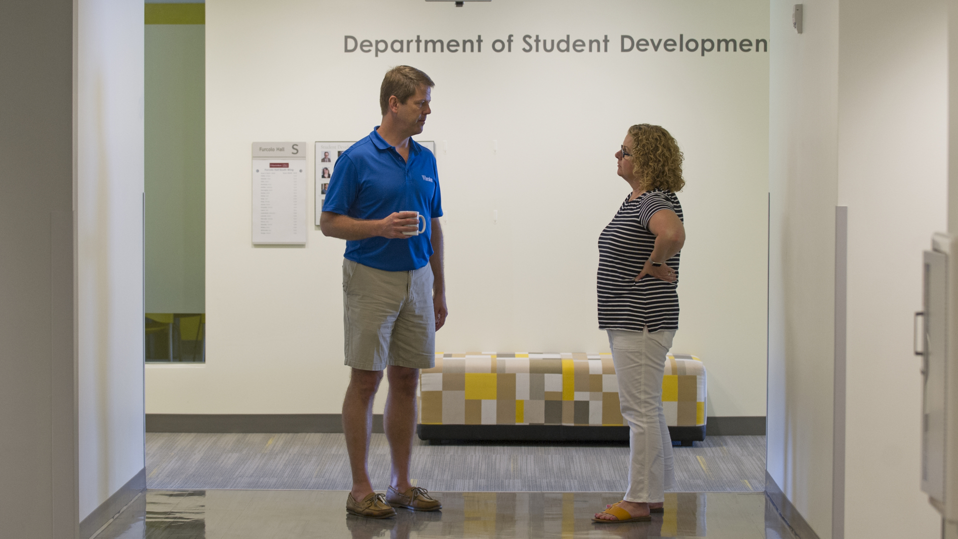 Ray and Judy standing in hallway in front of Student Development sign