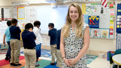 teacher smiling at front of classroom with young children