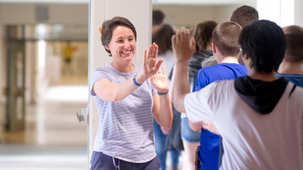 School counselor giving students high-fives in the hallway