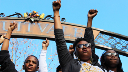 Students of color raise their fists in solidarity at a Black Lives Matter protest