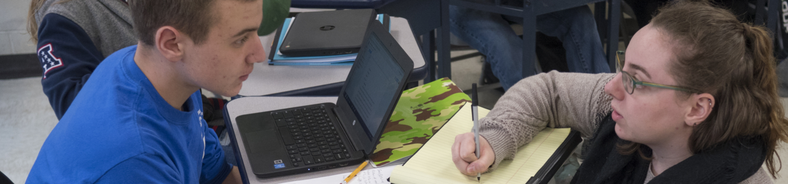 Teacher assisting student at desk with laptop