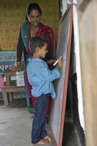 young student in Nepal pointing at chalkboard