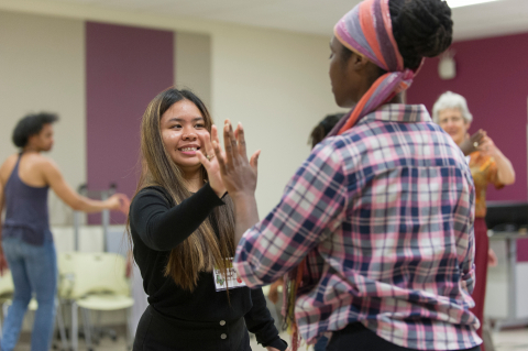 Two participants in an intergroup dialogue workshop high five