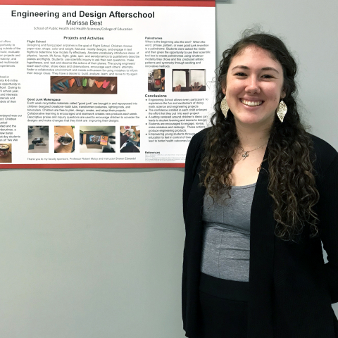"Marissa Best stands in front of her research poster entitled, ""Engineering and Design Afterschool"""