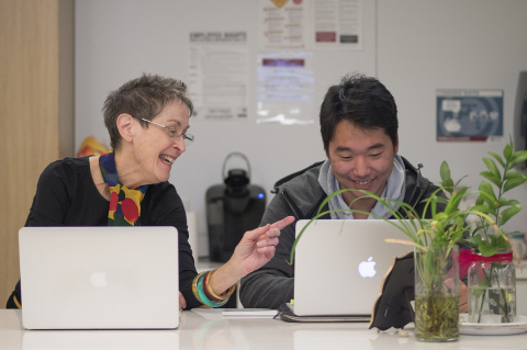 Sharon Edwards with student Chan Kim looking at laptop computers
