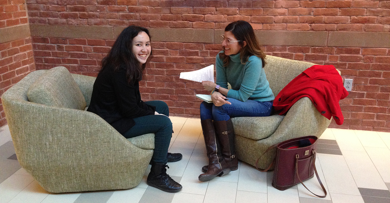 An alumna chats with a smiling student in the South College commons.