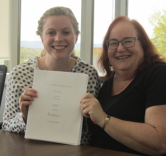 A smiling honors student poses with her advisor and completed thesis after a successful defense.