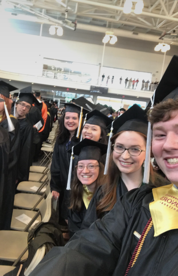 Selfie of smiling students at graduation in their regalia.