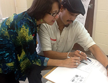 WMWP co-director Wilma Ortiz works with teacher-consultant Andrew Hafner at the annual Best Practices in the Teaching of Writing Conference on October 18, 2014.