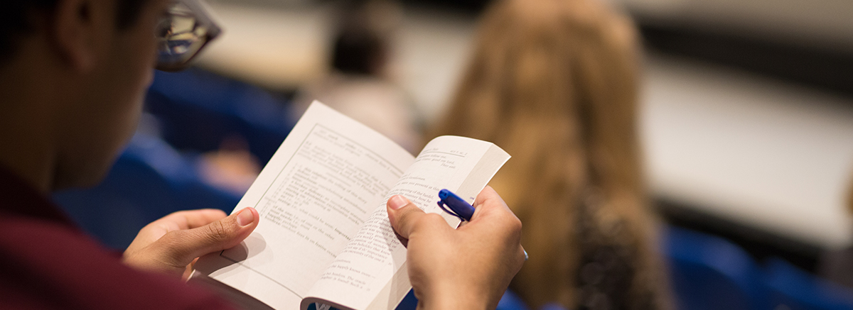 close up of student reading from a book in class