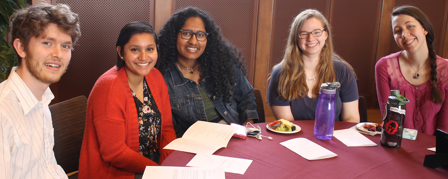 Smiling students seated around a table at the the English Department's Awards Ceremony.