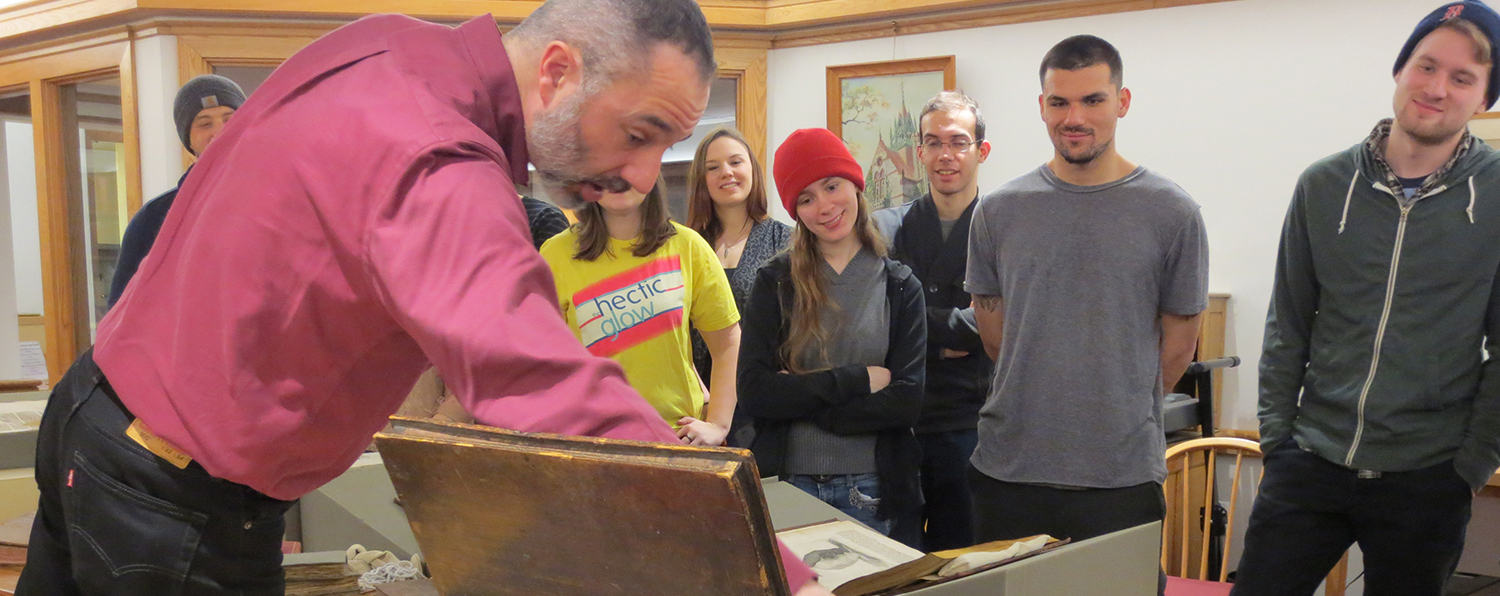 Smiling students look at rare books during a field trip.