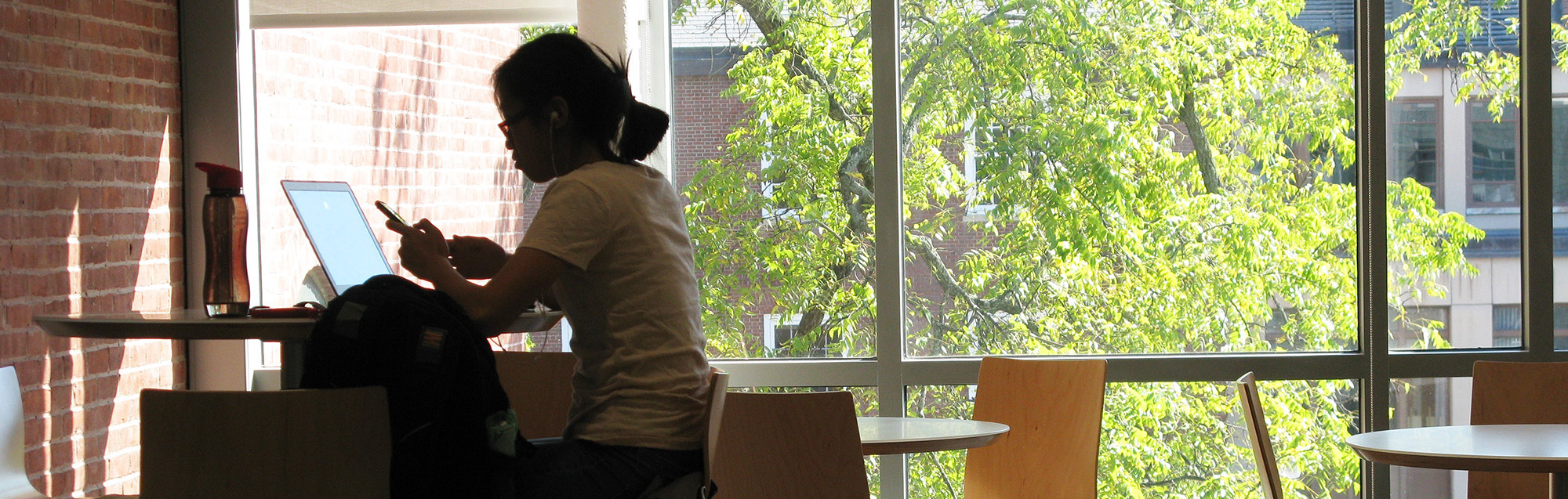 A student takes a break near a sunny window in South College.